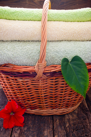 messy clothes: towels in a wicker basket next to the flowers and leaves of the plant on a wooden background