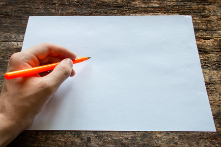 adult  body writing: lefty writes with a ballpoint pen on a sheet of paper on wooden table International Lefthanders Day Stock Photo