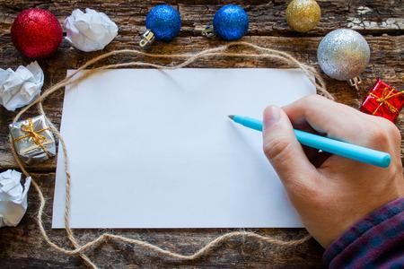 man schrijft een lijst van geschenken voor het nieuwe jaar
