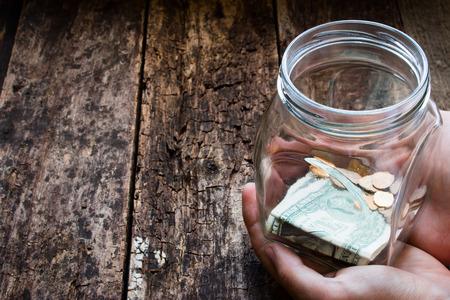 dinero: hombre que sostiene un frasco de vidrio para las donaciones