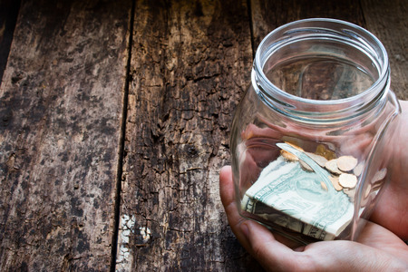 wealth: man holding a glass jar for donations Stock Photo