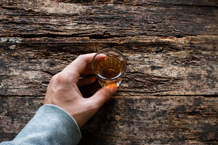 alcohol: man holding a glass of alcohol on a wooden background Stock Photo
