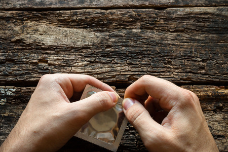 sex education: man opens a condom
