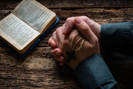 orando: hombre rezando ante un enfoque selectivo biblia Foto de archivo