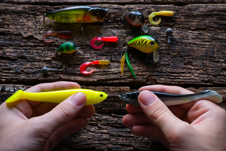 hand line fishing: man holding two lures for fishing with spinning