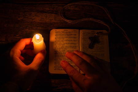 jesus word: man praying on the Bible in the light candles selective focus Stock Photo