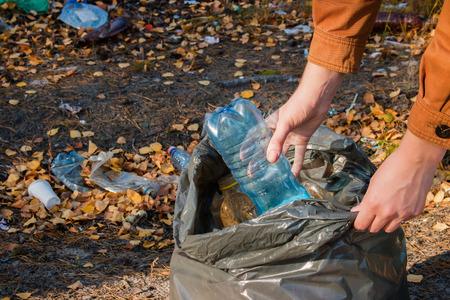 reciclar: mujer joven recoge la basura en el bosque Foto de archivo