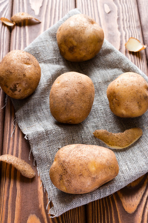 unpeeled: unpeeled potatoes on a gray napkin on a wooden table Stock Photo