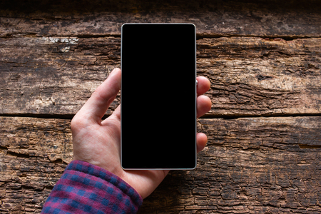 man holding a phone in his hand on the wooden background mockup Zdjęcie Seryjne