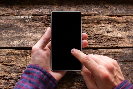 alzando la mano: hombre toca la pantalla en el teléfono en un fondo de madera maqueta Foto de archivo