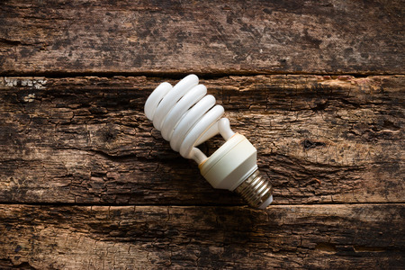 Energy saving light bulb on wooden background