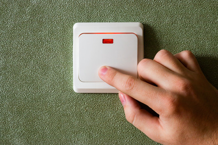 turning off: man turning off lights saves energy