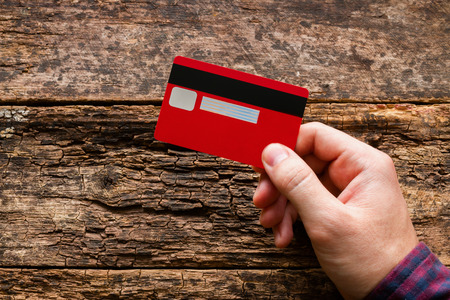 technology transaction: man holding a credit card on a wooden background
