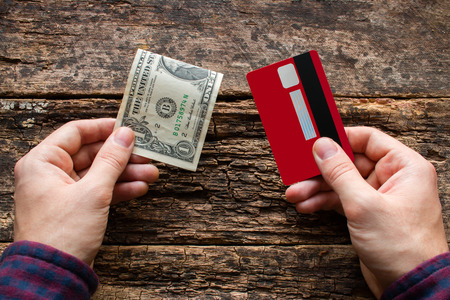 technology transaction: man holding credit card and money