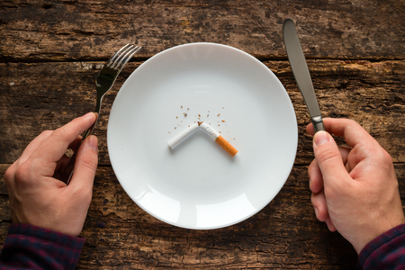 holding a knife: man holding a knife and fork next to a white plate with a cigarette Stock Photo