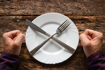man refuses to eat spoon and fork on a plate stacked in the shape of a cross Stock Photo - 48535326