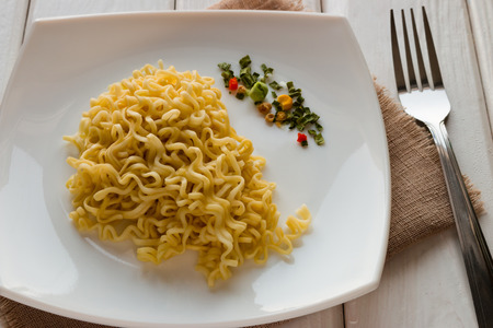 cooked instant noodle: Ramen on a white plate with dry vegetables