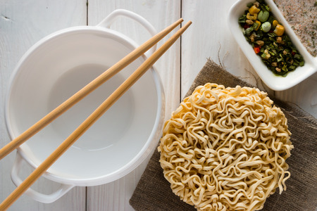 cooked instant noodle: bulonnitsa, noodles, spices and chopsticks on a white background