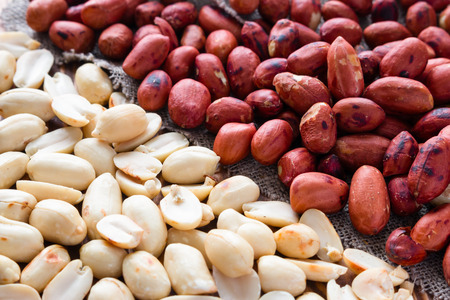 earthnuts: background of crude and refined roasted peanuts Stock Photo
