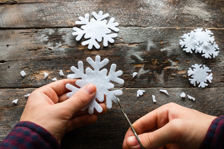 carves: man carves a snowflake on a wooden background