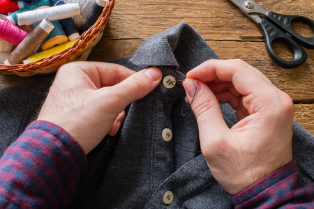 man sews a button to his shirt