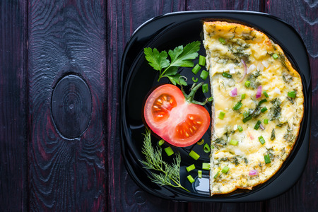 omlet: omelette on the black plate decorated with vegetables on a wooden background