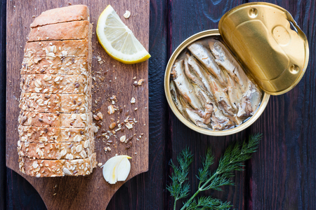 sprat: bread with seeds and sprat in the bank on a black background