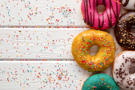 glazes: donuts in different glazes on wooden white background and space for text