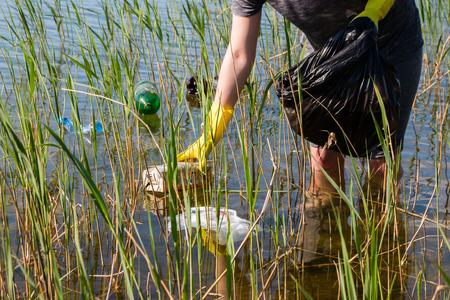 mundo contaminado: voluntarios muchacha limpia el estanque de la basura enfoque selectivo
