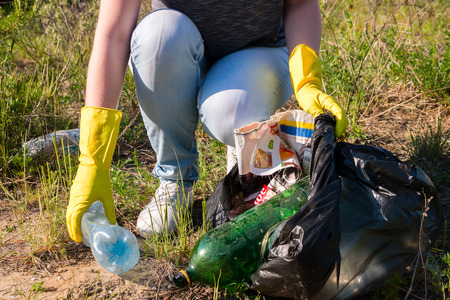La muchacha voluntaria en los guantes amarillos recoge la basura enfoque selectivo Foto de archivo - 58553846