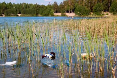 mundo contaminado: basura en el lago en el fondo de la playa