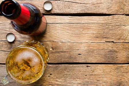 botella de vidrio y una jarra de cerveza ligera en un espacio de fondo de madera para el texto