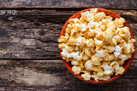 bowls of popcorn: Popcorn in a bowl on a wooden background with space for text