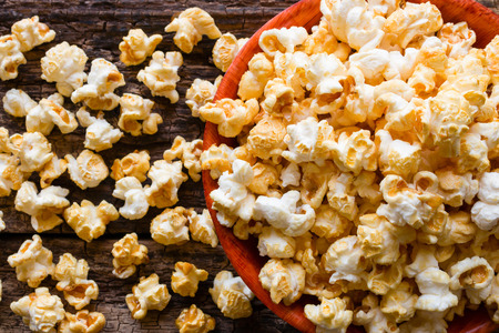 bowls of popcorn: popcorn with caramel on a wooden background close up