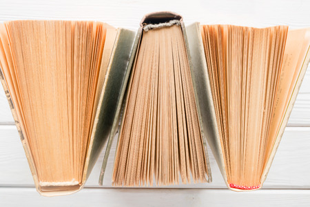 yellowed: Vintage books with yellowed pages on a white background closeup