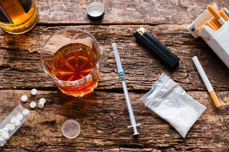Alcohol, cigarrillos, drogas, pastillas sobre un fondo de madera Foto de archivo - 60224899