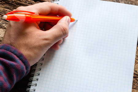 adult  body writing: left-handed man writes in a notebook Stock Photo