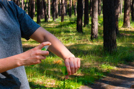 girl in the forest uses the spray against mosquitoes