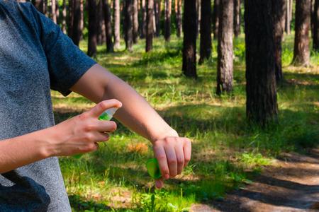 insecto: niña en el bosque utiliza el spray contra los mosquitos