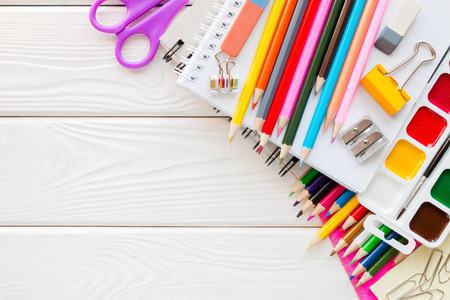 School stationery on a white wooden background and space for text