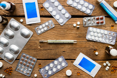 medical pills, antibiotics, nasal drops, a thermometer on a wooden background Stock Photo