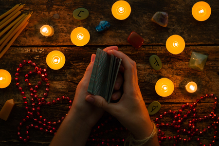 fortuneteller reads fortunes by tarot cards and candles on the background of the runes