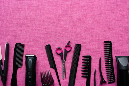 hairdressing tools on pink background and space for text