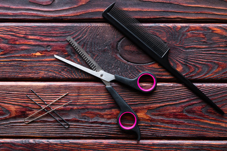 haircutting: scissors and comb hairdresser tools on a wooden background