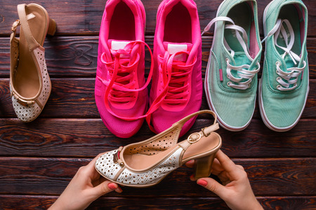 Girl chooses between the womens shoes and running shoes Stock Photo