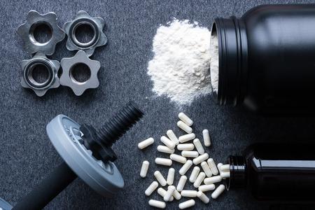 ダンベル、蛋白質とアミノ酸は、灰色の背景に 写真素材