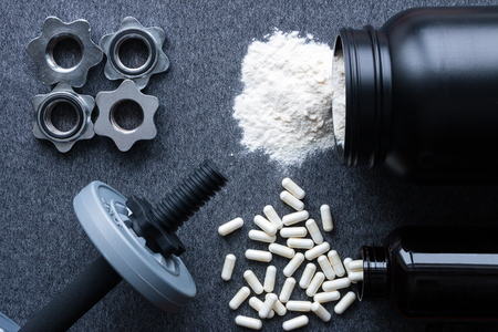 dumbbells, protein and amino acids on a gray background