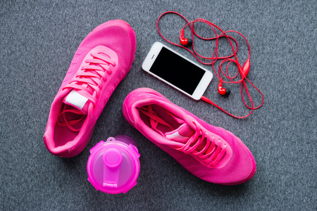 sports equipment - running shoes, a smartphone and a shaker