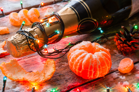 bottle of champagne, tangerine and Christmas decorations on the wooden background