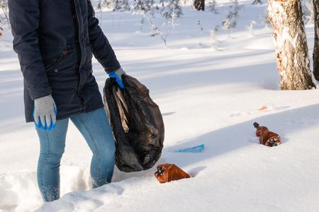 mundo contaminado: chica con una bolsa de basura en el bosque de invierno